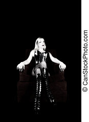 Older Blond Woman Sitting In Corset Stockings And Boots