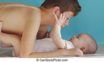 Older brother kissing baby. Sweet siblings love. Brother care baby infant at home
