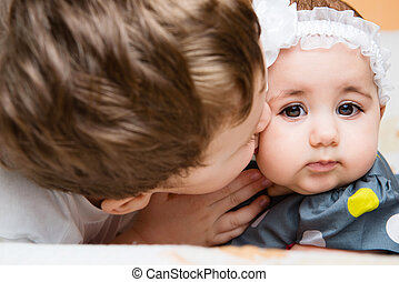 Older brother kissing his baby sister