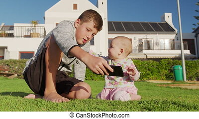 Older brother shows phone to little baby sister sitting on the grass.