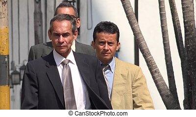Older Business Men Walking On Sidewalk