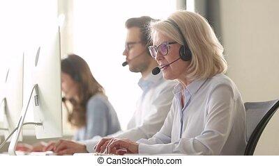 Older business woman wear wireless headset working in customer service