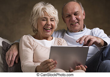 Happy elderly marriage having fun with new technology. Sitting on a sofa and using tablet