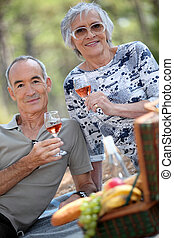 Older couple drinking rose wine with a picnic