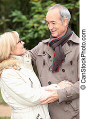 Older couple embracing on a winter's stroll