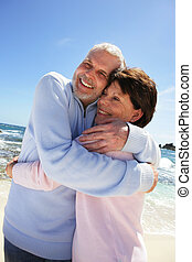 Older couple hugging on a beach
