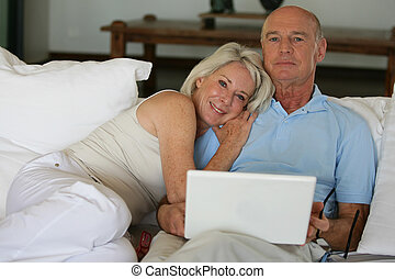 Older couple sitting on a sofa with a laptop
