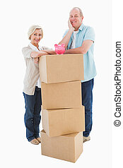 Older couple smiling at camera with moving boxes and piggy...