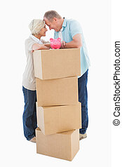 Older couple smiling at each other with moving boxes and...