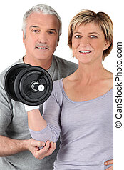 Older couple using gym weights