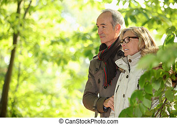 Older couple walking in the woods