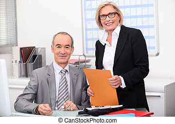Older couple working in an office