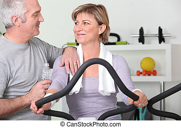 Older couple working out in a gym