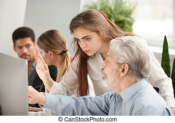 Older employee asking young manager question about online comput