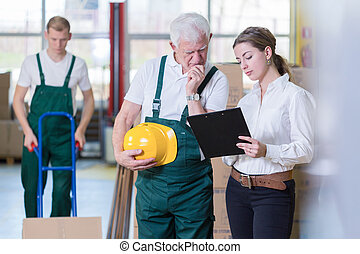 Older employee - Older warehouse employee and his young boss...
