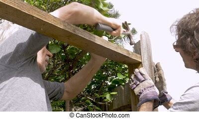 Older father and son repairing a fence with a hammer and...