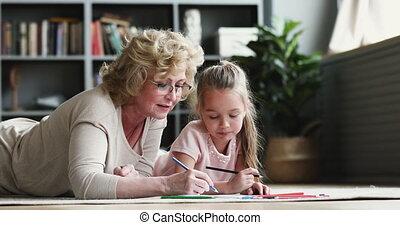 Older grandmother teaching preschool granddaughter drawing ...