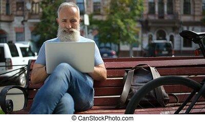 Older greyhaired man enjoying working outside - Positive...