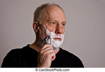 An older bald man in a black shirt shaving