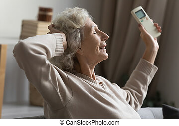 Older hoary woman resting on sofa, turning on air conditioner.