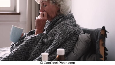 Older ill woman holding handkerchief blowing nose sitting in bed at home with cold remedy. Sick elder lady got flu virus having grippe symptom. Seniors respiratory diseases and antiviral drugs concept