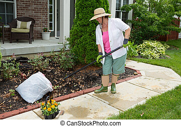Older lady doing cleaning work in the yard preparing a ...