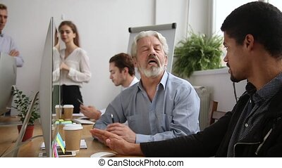 Older male mentor helping teaching new employee training...