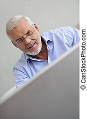 Older man at a laptop