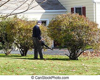 older man blowing leaves