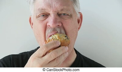 older man eating blueberry muffin - front view of man eating...