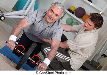 Older man exercising with a personal trainer