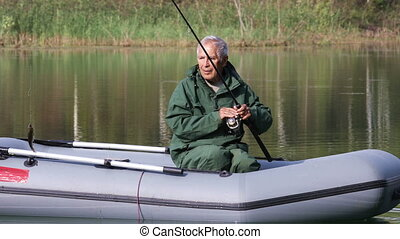 Older man fishing in a boat - Retired fisherman fishing on...