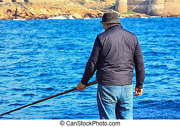 older man fishing on the shores of the sea with a cane