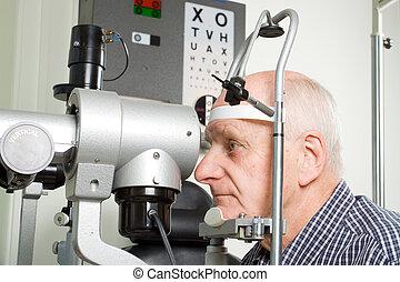 An older man taking an eye test examination at an opticians clinic