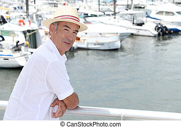 Older man in a straw panama hat standing by a marina