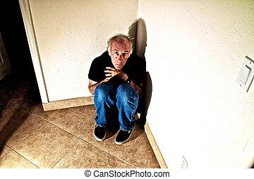older man in empty room terrified