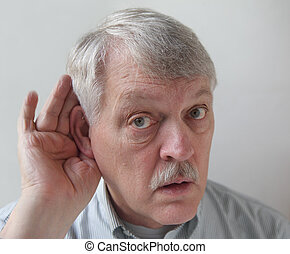 senior male cups his ear in order to hear better