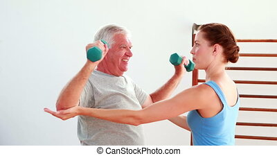 Older man lifting hand weights with the help of his...