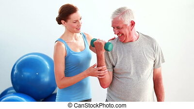 Older man lifting hand weights with the help of his trainer...