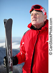 Older man on a mountain with skis