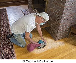 Older man sanding floor