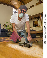 Older man sanding floor