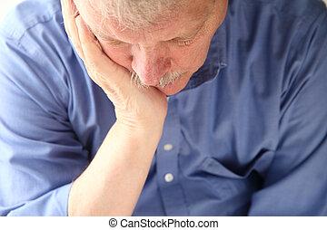 older man slumped in depression - unhappy senior man...