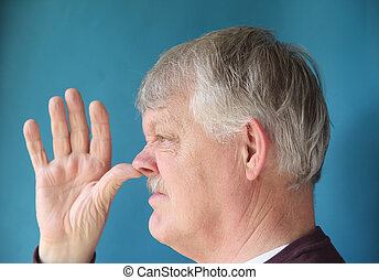 older man thumbs his nose