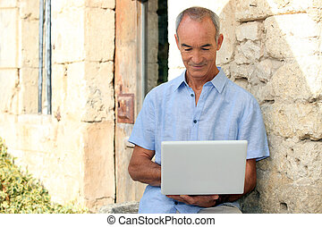 Older man using a laptop computer outside a lovely stone building