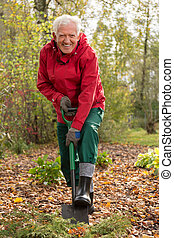Older man using a shovel in garden