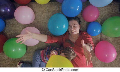 Older mother plays with her daughter in colorful balls lying on couch. Shot top