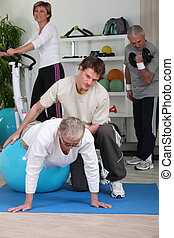 Older people working out with a personal trainer in a gym