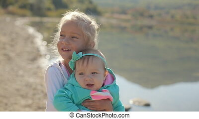 Older sister holds on hands junior near the lake, comes...