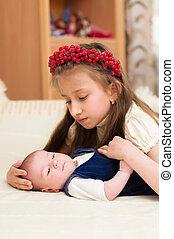Older sister hugging baby